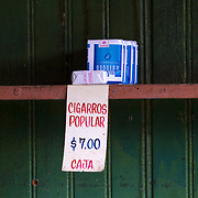 Cuban cigarettes  for sale ata government ration store for 7 CUP or National currency.   Every Cuban family registers with a local supply store, where they can use a libreta or ration book. The stores are just limited in quantity but also limited in the variety of items it has available. Cubans manage their daily life waiting for in line, riding overcrowded busses or walking to their destination. <br /> Photography by Jose More
