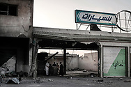 Misrata's residents survey a destroyed Gadhafi's army tank that was hiding from NATO air strike inside a car dealer showroom on Tripoli avenue. 26 May 2011.