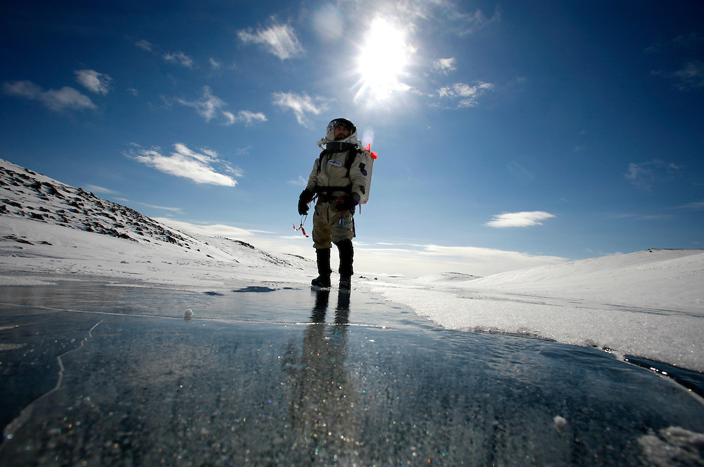 Ryan Kobrick  27 walking on the frozen Stanford Lake [422150E, 8375240N] during an E V A (Extravehicular Activity) on Saturday, June 2, 2007...Mars flashline Mars arctic (FMARS)..On Devon Island in the high Canadian Arctic a group of sciences from the USA & Canada is gathering for four month to search watt human being can do on mars planet..The four month mission will be the first time that a simulated Mars mission has ever been conducted for such a long duration..The crow of volunteers includes some biologist geologist and other nether scientist researches...They chose Devon Island in Canada because it simulated the acclaim on the planet Mars, for getting the filling of being on Mars and to challenge the research and to make it close as they can to the conditions on the planet they wear spies suit and live isolated in the laboratory for four month..The man person that ran the project is Dr Robert Zabrin that believe that this project can lied to find ways to search for life on Mars and maybe to fined a way that human being will be able to live on the planet...This project is privet projects that cooperate with several universities around the world...