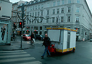 A vendor moves his hot dog cart through the Vesgterbro neighborhood of Copenhagen, Denmark