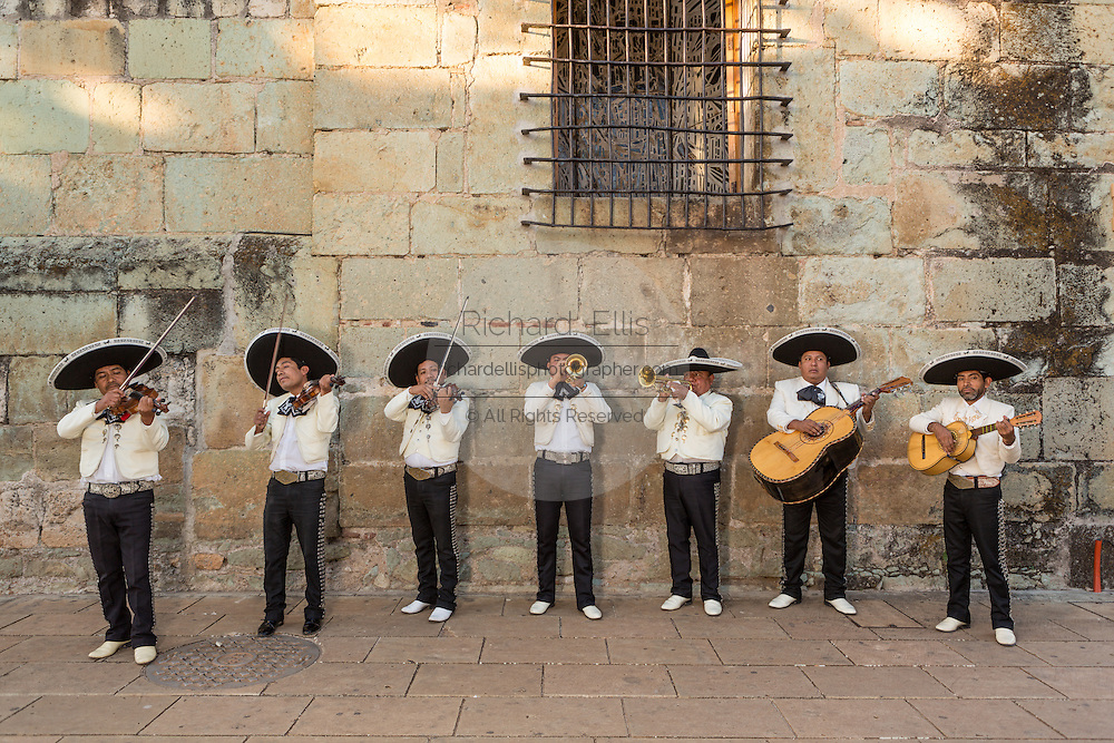 A Mexican mariachi band dressed in traditional charro costume perform in front of the Santo Domingo de Guzmán Church November 5, 2013 in Oaxaca, Mexico.