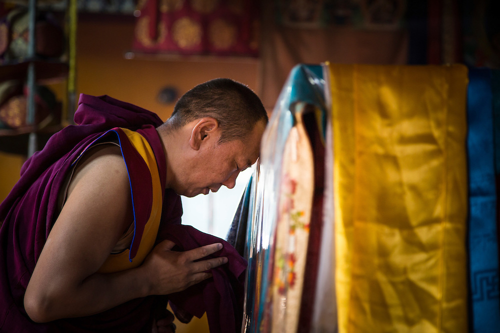 "A monk participates during morning prayers at the Gandantegchinlen Monastery, known as the Gandan Monastery, a Tibetan-style monastery in the Ulaanbaatar Mongolian, on July 23, 2012.  The Tibetan name translates to the ""Great Place of Complete Joy."" It currently has over 150 monks in residence. © 2012 Tom Turner Photography."
