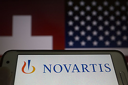 May 25, 2019 - Asuncion, Paraguay - Logo of Novartis, a Swiss multinational pharmaceutical company, is seen on a smartphone screen against Switzerland and United States flags unfocused on background. (Credit Image: © Andre M. Chang/ZUMA Wire)