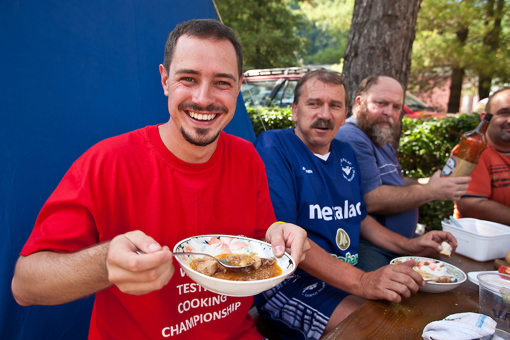 Visitors to the 2011 World Testicle Cooking Championship sample some goulash, Ovcar Banja, Serbia.