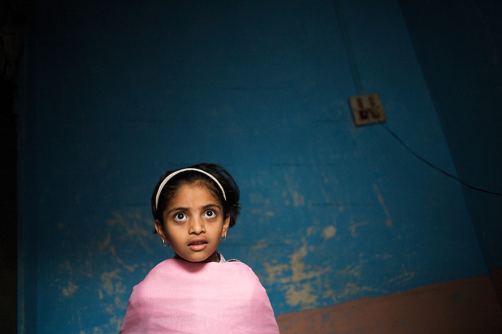 """At home, Vasanti's  HIV positive daughter Shruda, 10. Vasanti Shinde, 26, works for the Save Foundation. <br /> <br /> Like many of the women who work for and with UNDP partners the Save Foundation, Vasanti Shinde, age 26, only found out that she was HIV positive after her husband became seriously ill with an AIDS-related illness five years ago. Vasanti's husband subsequently died. Vasanti now lives with her two younger daughters Shrudha, age 10, and Vrinda, 8, in the one-room home of her brother in Sangli city. Vasanti's elder daughter, eleven year old Shubhada is being brought up by her paternal grandmother and sees her mother during holidays. Vasanti knows that Shubhada is HIV negative and Shruda is positive but anxiety over the result means that she refuses to have Vrinda tested for HIV. For a monthly income of Rs.3500, Vasanti works as a field officer and counselor for the Save Foundation. She works in the positive-people's pharmacy for no pay. Her work with the Save Foundation entitles her access to a credit union which provides low interest loans covering medical expenses. Though first-line drugs and homeopathic medicine keep Vasanti healthy, she is prone to infection and recently suffered a bout of influenza. Vasanti is completely open about her HIV status and most of her neighbours know that she is HIV positive. Vasanti says that """"I used to feel like I was going to die. Now, because of the Save Foundation, I feel like I'm going to live."""" <br /> <br /> Photo: Tom Pietrasik<br /> Sangli, Maharashtra. India<br /> August 28th 2008"""