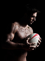 one caucasian sexy topless man portrait holding a rugby ball on studio black background a rugby ball on studio black background