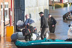©Licensed to London News Pictures 21/12/2019. <br /> Yalding ,UK. Resident getting off a boat with his bags.  Little Venice Country Park and Marina in Yalding has been severely flooded, residents of the lodge and caravan community are having to use boats to get on and off the site. The River Medway in Yalding, Kent has bursts its banks causing severe flooding to the village.   Photo credit: Grant Falvey/LNP