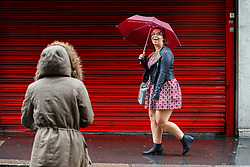 © Licensed to London News Pictures. 26/08/2015. London, UK. People shelter themselves during heavy rain in central London on Wednesday, August 26, 2015. Photo credit: Tolga Akmen/LNP