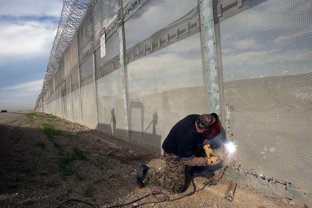A U.S. Border Patrol employee welds a portion of the fence separating Tijuana, Mexico from San Diego, California after it was cut by smugglers the previous night. The employee said he repairs at least five sections of the fence daily. Please contact Todd Bigelow directly with your licensing requests.