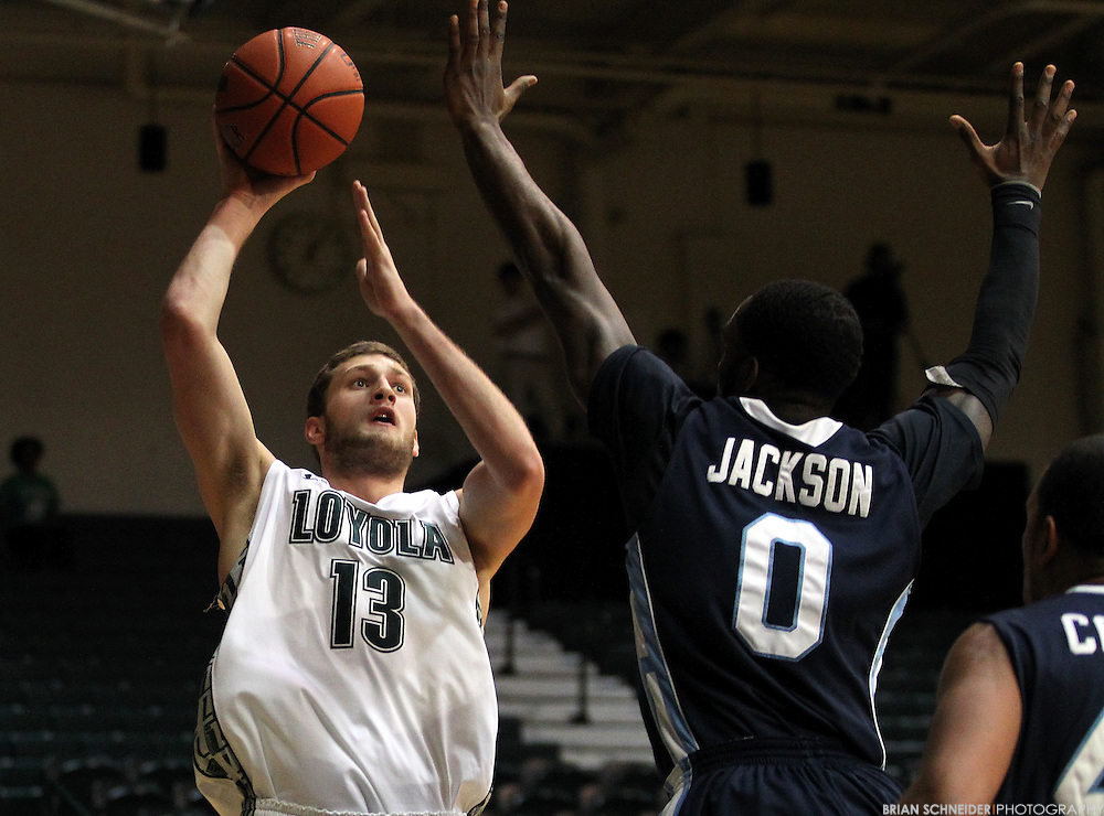 January 6, 2012; Baltimore, MD, USA; Loyola Maryland Greyhounds forward Franz Rassman (13) attempts a layup against Saint Peter's Peacocks forward Patrick Jackson (0) in the first half at Reitz Arena in Baltimore, MD. Mandatory Credit: Brian Schneider-www.ebrianschneider.com
