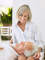 Man resting head on woman's lap sitting on verandah