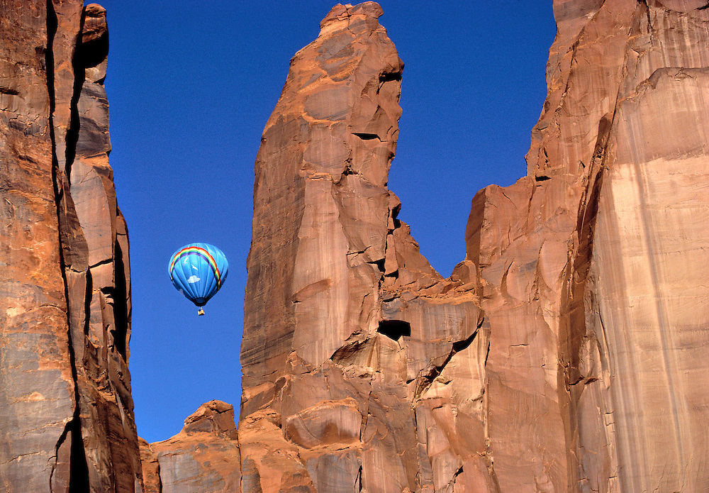 A colorful hot-air balloon rises above the desert in Monument Valley, Utah.