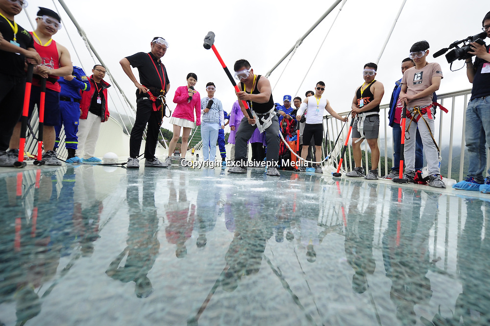 ZHANGJIAJIE, CHINA - JUNE 25:<br /> <br /> A visitor strikes the glass-bottomed bridge with a hammer for a safety test at Zhangjiajie Grand Canyon on June 25, 2016 in Zhangjiajie, Hunan Province of China. World\'s tallest and longest glass-bottomed bridge has been completed and took a global broadcast through television and internet medias to show its safety. More than thirty cit<br /> ©Exclusivepix Media