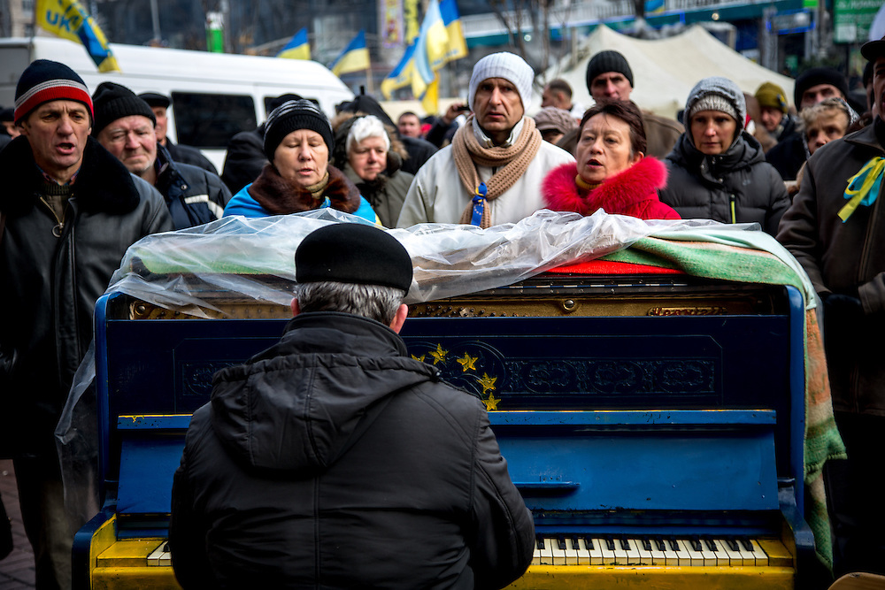 A group of protesters sing the Ukrainian anthem on the Independance Square, accompanied by a musician playing on a blue piano decorated with the European flag.