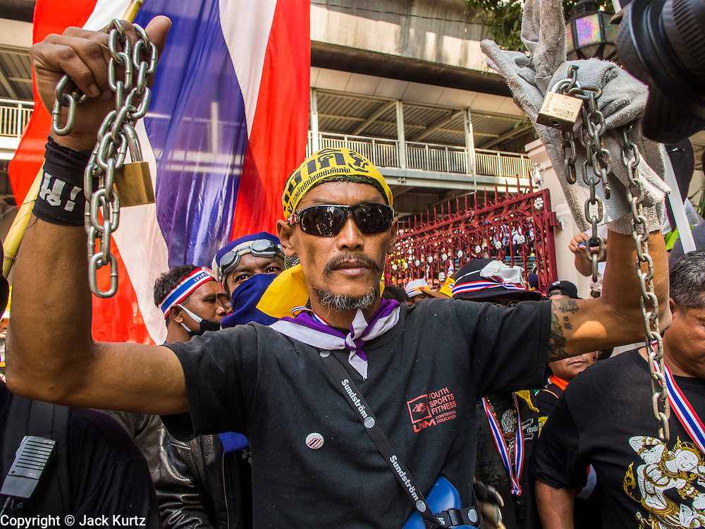 04 DECEMBER 2013 - BANGKOK, THAILAND:  An anti-government protestor holds up a chain and locks during a protest at police headquarters. Several hundred anti-government protestors tried to occupy Royal Thai Police Headquarters on Rama I Road in central Bangkok Wednesday. The protest was one of the continuing protests against the government of Prime Minister Yingluck Shinawatra. Police commanders allowed protestors to tear down police barricades and ordered riot police to lay down their shields. Protestors then chanted anti-government slogans and called on police to turn against the government before forming a motorcade and leaving the area. Anti-government protests have gripped Bangkok for nearly a month and protestors vow to continue their actions. Protests Wednesday were much smaller and more peaceful than protests earlier in the week.     PHOTO BY JACK KURTZ