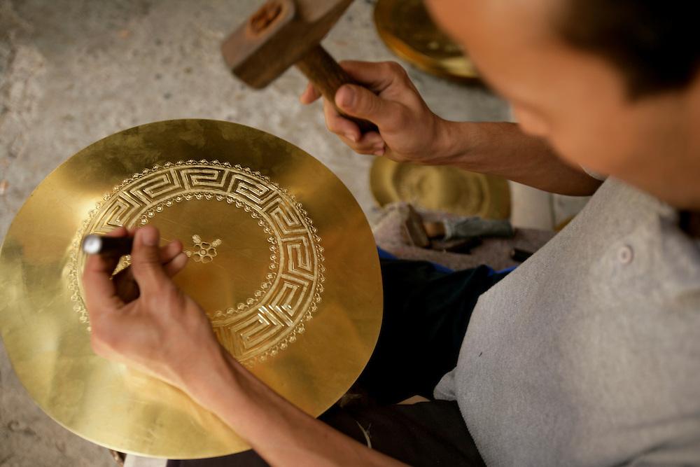 Artisan manufacturing copper plates in a shop inside Fez medina.