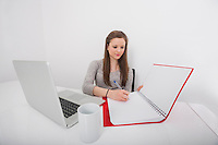 Businesswoman writing in book at office desk
