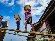 22 FEBRUARY 2017 - BAN LAEM, PETCHABURI, THAILAND: Salt workers load a truck during the salt harvest in Petchaburi province of Thailand, about two hours south of Bangkok on the Gulf of Siam. Salt is collected in coastal flats that are flooded with sea water. The water evaporates and leaves the salt in large pans. Coastal provinces south of Bangkok used to be dotted with salt farms, but industrial development has pushed the salt farms down to remote parts of Petchaburi province. The harvest normally starts in early February and lasts until early May, but this year's harvest was delayed by a couple of weeks because of unseasonable rain in January that flooded many of the salt collection ponds.    PHOTO BY JACK KURTZ