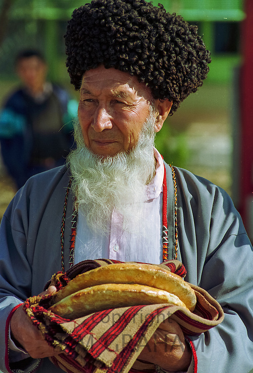 Old man wearing traditional Astrakhan hat and with welcome gift of bread in town of Mary in Turkmenistan