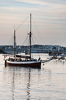 Sailboat floats by the Johnson Street Bridge in the Inner Harbour of Victoria, BC on a summer evening.