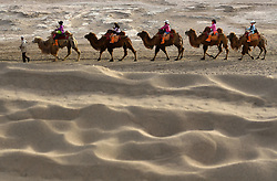 May 1, 2019 - Dunhuang, China - Tourists ride camels in the Crescent Spring and Mingsha Sand Dune scenic area in Dunhuang, northwest China's Gansu Province, on May 1, 2019, the first day of the four-day May Day holiday. (Credit Image: © Xinhua via ZUMA Wire)