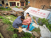 02 AUGUST 2015 - BHAKTAPUR, NEPAL:  People gather their bedding in a small Internal Displaced Person (IDP) camp at Durbar Square in Bhaktapur for people left homeless by the Nepal earthquake. The Nepal Earthquake on April 25, 2015, (also known as the Gorkha earthquake) killed more than 9,000 people and injured more than 23,000. It had a magnitude of 7.8. The epicenter was east of the district of Lamjung, and its hypocenter was at a depth of approximately 15km (9.3mi). It was the worst natural disaster to strike Nepal since the 1934 Nepal–Bihar earthquake. The earthquake triggered an avalanche on Mount Everest, killing at least 19. The earthquake also set off an avalanche in the Langtang valley, where 250 people were reported missing. Hundreds of thousands of people were made homeless with entire villages flattened across many districts of the country. Centuries-old buildings were destroyed at UNESCO World Heritage sites in the Kathmandu Valley, including some at the Kathmandu Durbar Square, the Patan Durbar Squar, the Bhaktapur Durbar Square, the Changu Narayan Temple and the Swayambhunath Stupa. Geophysicists and other experts had warned for decades that Nepal was vulnerable to a deadly earthquake, particularly because of its geology, urbanization, and architecture.      PHOTO BY JACK KURTZ