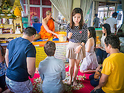 24 FEBRUARY 2013 - BANGKOK, THAILAND: A family receives blessings from a Buddhist monk at Wat Hua Lamphong. Wat Hua Lamphong is a Royal Buddhist temple, third class, in the Bang Rak District of Bangkok, Thailand. It is located on Rama IV Road, approximately 1 km from the city's main Hua Lamphong railway station. An entrance to Sam Yan Station on the Bangkok metro (subway) is located outside the main entrance to the temple compound on Rama IV. Wat Hua Lamphong was renovated in 1996 to mark the 50th anniversary of the ascension to the throne of King Bhumibol Adulyadej (Rama IX) in 1996. The royal seal of what became known as the Kanchanapisek, or Golden Jubilee, year, showing two elephants flanking a multi-tiered umbrella, are featured in the temple's remodeling.     PHOTO BY JACK KURTZ