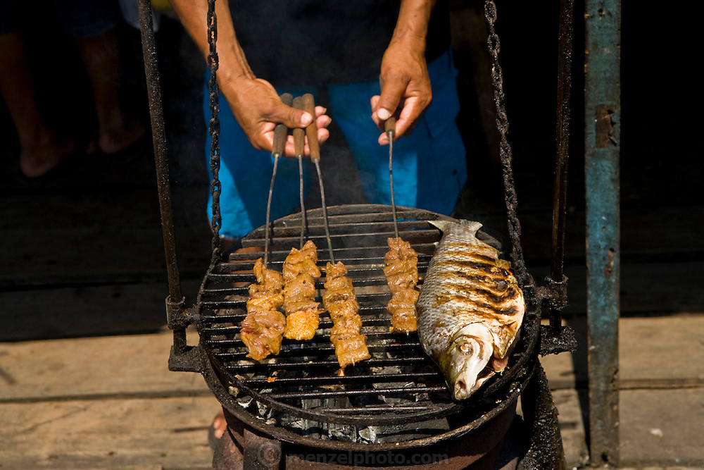 A fisherman grills fresh fish and chicken on the Solimoes River in Manacapuru, Brazil.