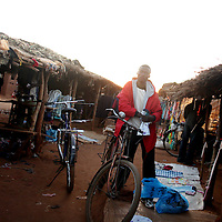 A young man stands next to his bike during the closing hour of an informal market in Chimoio, Mozambique.