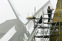 06-10-2005; SCHERMERHORN:Rietdekken in de mist. Rietdekker Sprenkeling is aan het werk aan Bovenmolen E in Schermerhorn. De watermolen, een 8-kante grondzeiler binnenkruier, is eigendom van de Stichting De Schermer Molens en wordt geheel gerestaureerd. Op de achtergrond de museummolen, middenmolen D.