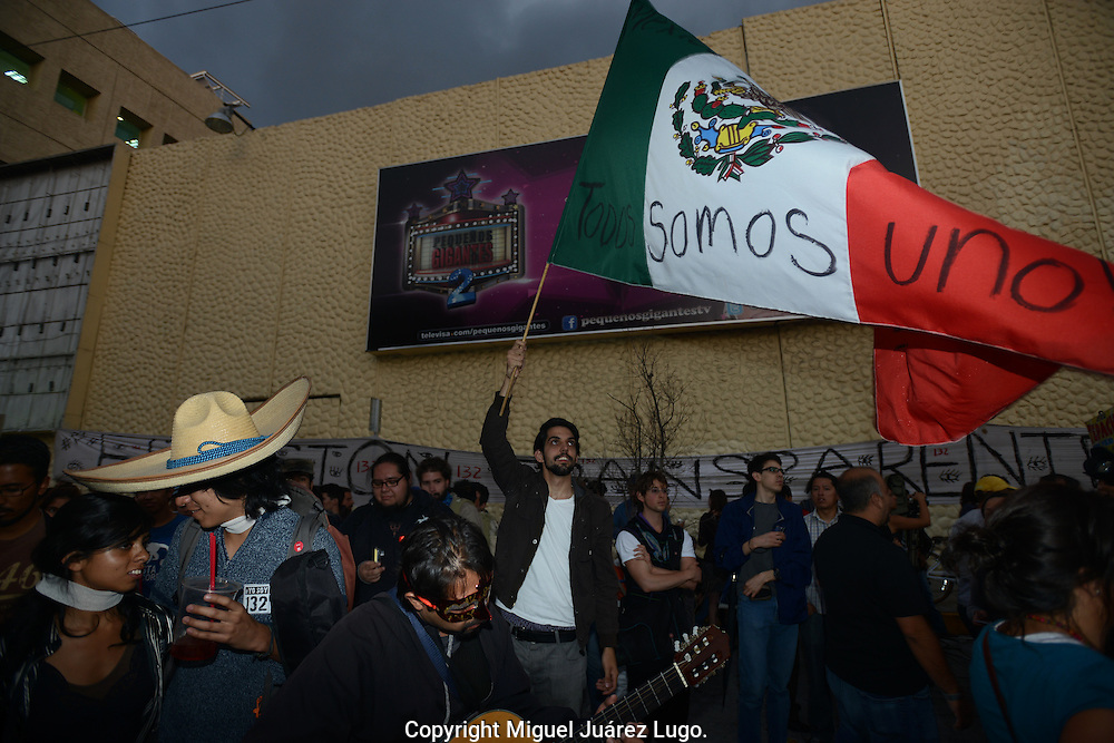 Mexico City--Antonio Antollini, leader of a students group within the movement #YoSoy132 waves a Mexican flag during a protest against political corruption and leading PRI party presidential candidate Enrique Peña Nieto. (PHOTO: MIGUEL JUAREZ LUGO)