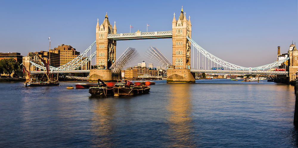 Multiple exposure stock photograph of London's Tower Bridge with the bridge opening in stages to let through an old sailing barge