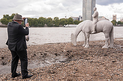 "© Licensed to London News Pictures. 02/09/2015 London, UK. A man takes a photo of the art installation entitled ""The Rising Tide"" (comprising four horse-riders on horses with petroleum pumps for heads) by the underwater eco-sculptor Jason deCaires Taylor, which stands on the foreshore of the River Thames in Vauxhall and is revealed with each low tide.  The installation aims to question man's reliance on fossil fuels and is part of this year's Totally Thames festival. Photo credit : Stephen Chung/LNP"