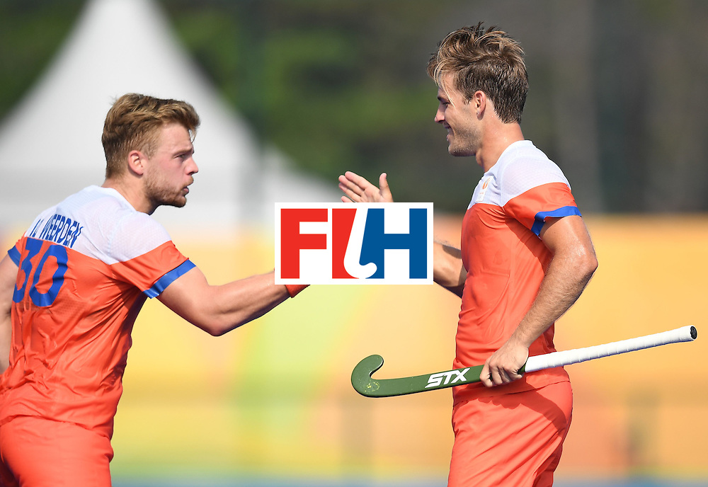 Netherland's Jeroen Hertzberger (R) celebrates scoring a goal with teammate Mink van der Weerden during the men's field hockey Netherlands vs Canada match of the Rio 2016 Olympics Games at the Olympic Hockey Centre in Rio de Janeiro on August, 9 2016. / AFP / MANAN VATSYAYANA        (Photo credit should read MANAN VATSYAYANA/AFP/Getty Images)