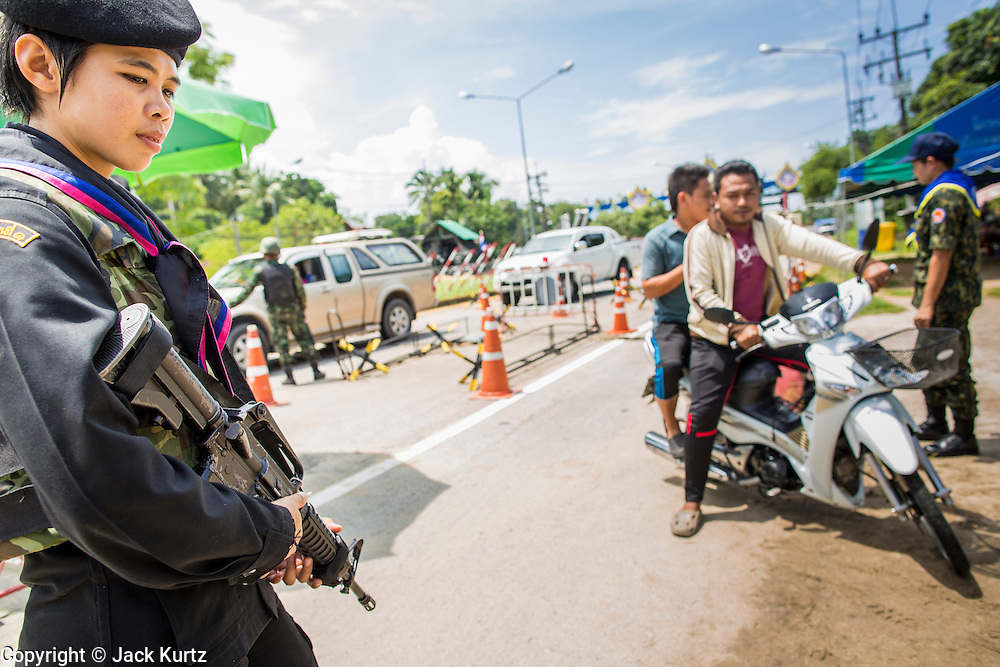 "25 OCTOBER 2012 - TAK BAI, NARATHIWAT, THAILAND: AThai woman Ranger (paramilitary operating under Army command) at a checkpoint in Tak Bai, Thailand. The ""Tak Bai Incident"" took place on Oct. 25 in Tak Bai, Narathiwat, Thailand during the Muslim insurgency in southern Thailand. On that day, a crowd gathered to protest the arrest of local residents. Police made hundreds of arrests during the protest and transported the arrested to Pattani, about two hours away, in another province. They were transported in locked trucks and more than 80 people suffocated en route. This enraged local Muslims and shocked people across Thailand. No one in the Thai army accepted responsibility for the deaths and no one was ever charged. In the past, the anniversary of the incident was marked by protests and bombings. This year it was quiet. More than 5,000 people have been killed and over 9,000 hurt in more than 11,000 incidents, or about 3.5 a day, in Thailand's three southernmost provinces and four districts of Songkhla since the insurgent violence erupted in January 2004, according to Deep South Watch, an independent research organization that monitors violence in Thailand's deep south region that borders Malaysia.   PHOTO BY JACK KURTZ"