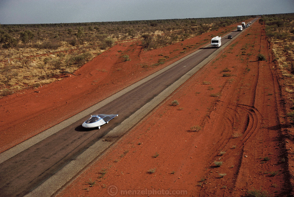 Sunraycer, General Motors' entry for the Pentax Solar Car Race, the first international solar-powered car race, which began in Darwin, Northern Territories on November 1st, 1987 and finished in Adelaide, South Australia. Sunraycer (bottom left) is shown here on the 3rd day of the race, moving along a dead straight section of the Stuart Highway (Route 87) in the outback 100 km south of Devil's Marbles. Sunraycer was the eventual winner, taking 5 1/2 days to complete the 1,950 miles, traveling at an average speed of 41.6 miles per hour. Sunraycer's power source was an array of 7,200 photovoltaic cells, joined to form a hood over the top and back of the vehicle. (1987) .