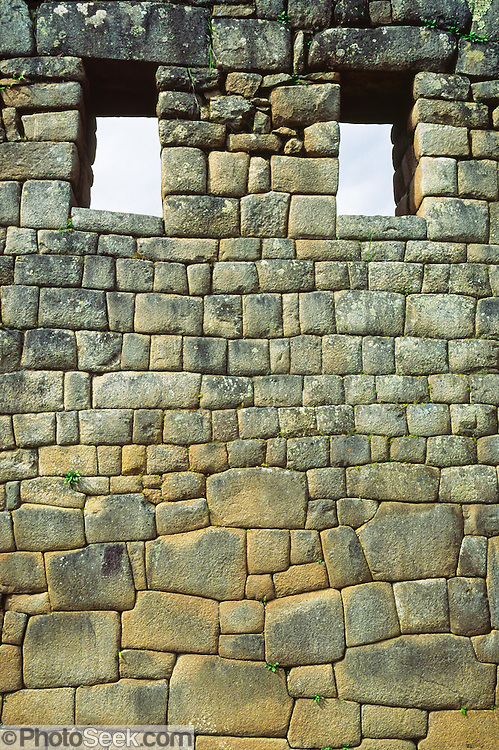 """The Incas finely crafted this stone wall with windows at Machu Picchu, a magnificent archeological site in the Cordillera Vilcabamba, Andes mountains, Peru, South America. Machu Picchu was built around 1450 AD as an estate for the Inca emperor Pachacuti (14381472). Spaniards passed in the river valley below but never discovered Machu Picchu during their conquest of the Incas 1532-1572. The outside world was unaware of the """"Lost City of the Incas"""" until revealed by American historian Hiram Bingham in 1911. Machu Picchu perches at 2430 meters elevation (7970 feet) on a well defended ridge 450 meters (1480 ft) above a loop of the Urubamba/Vilcanota River ( Sacred Valley of the Incas). UNESCO honored the Historic Sanctuary of Machu Picchu on the World Heritage List in 1983."""