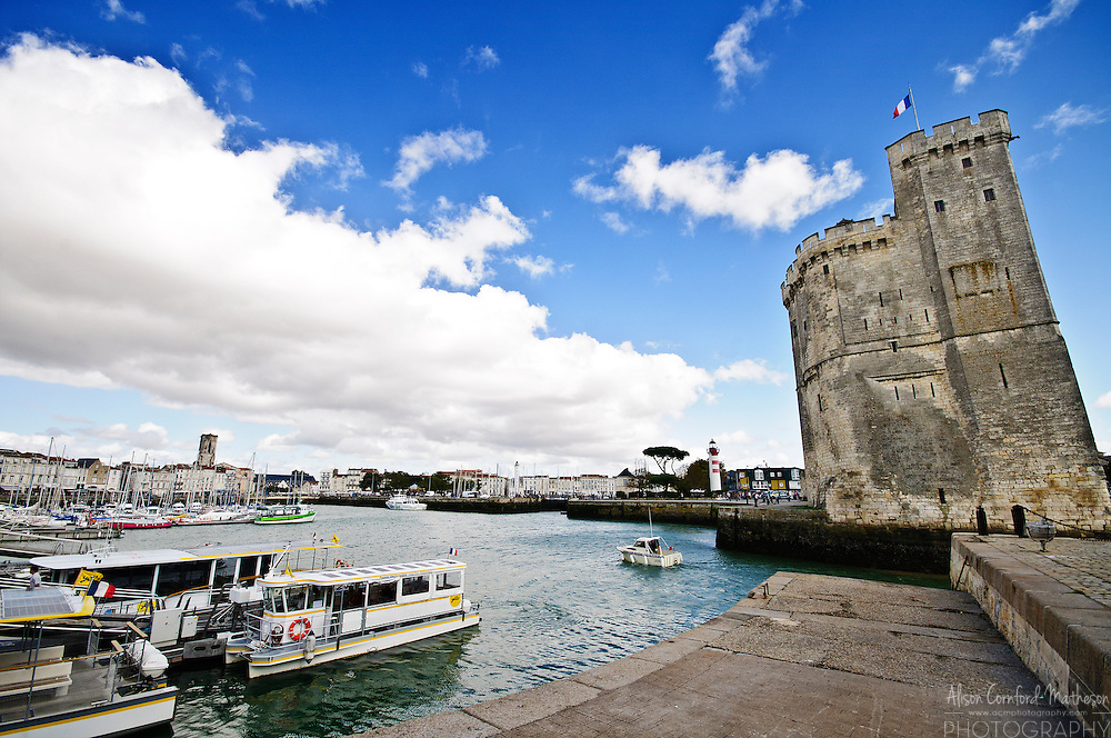 The bustling Vieux-Port (old port) of La Rochelle, France is busy with locals and tourists on a sunny day.