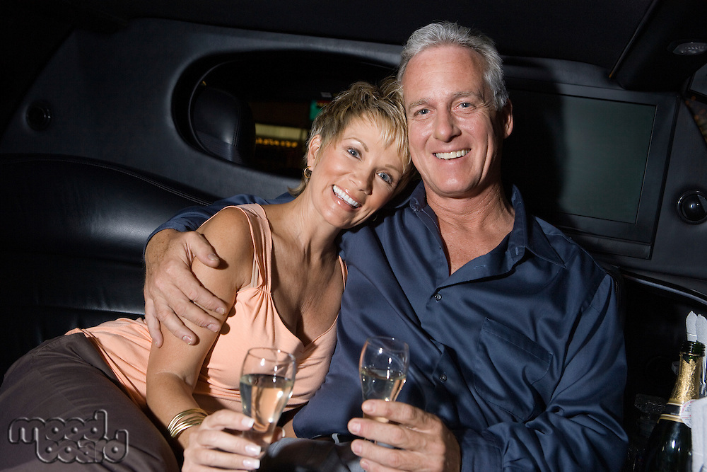 Middle-aged couple sitting on back seat of limousine and drinking champagne, portrait