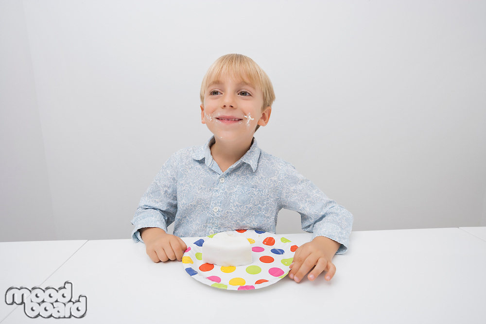Smiling boy with cake slice in plate on table at home