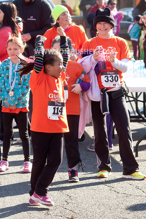 Cornwall-on-Hudson, New York - A girl from the Girls on the Run Hudson Valley program celebrates after finishing the Cornwall Lions Club Fall Harvest Race 5K on Nov. 10, 2013. Girls on the Run is a national program with a mission of helping girls to be joyful, healthy and confident using an experience-based curriculum which creatively integrates running.