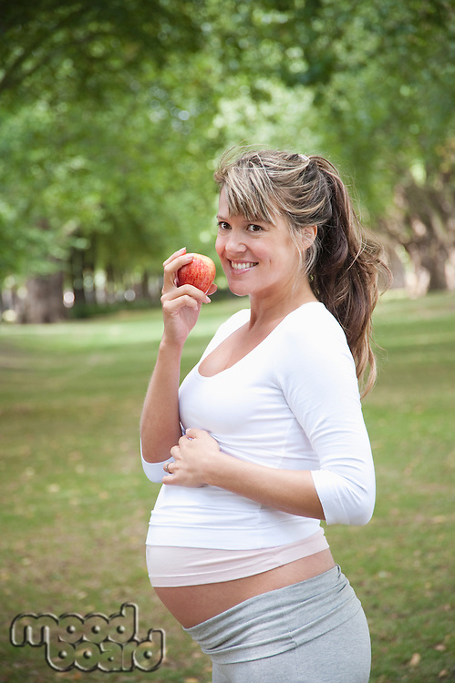 Pregnant woman in park eating apple