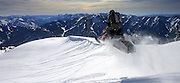 Todd Williams pops off a cornice with the Wyoming Range in the background outside of Alpine, Wyoming.