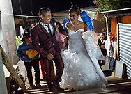 Rosalino and Sabina laugh as the two struggle to find the right way to lock arms as they are announced at their wedding reception. Nick Wagner / Alexia Foundation