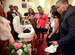 07 September 2013. New Orleans, Louisiana.<br /> Funeral service for 1 year old toddler Londyn Unique Reed Samuels, shot to death August 29th.<br /> Andrea Samuels, (at right, Black and white dress - 22 yrs old) mother of the victim pays her final respects to her daughter at the New Hope Baptist Church. The infant Londyn was shot by thugs whilst in the arms of her babysitter, the intended victim who was holding Londyn whilst walking down the street at the time of the assault. 2 thugs are in custody.<br /> Photo; Charlie Varley