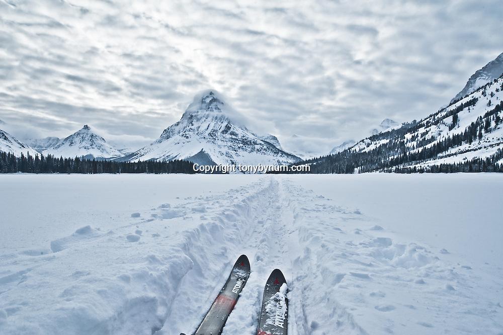 glacier national park, ski tracks on frozen two medicine pake, sinopah mountain, glacier national park, montana