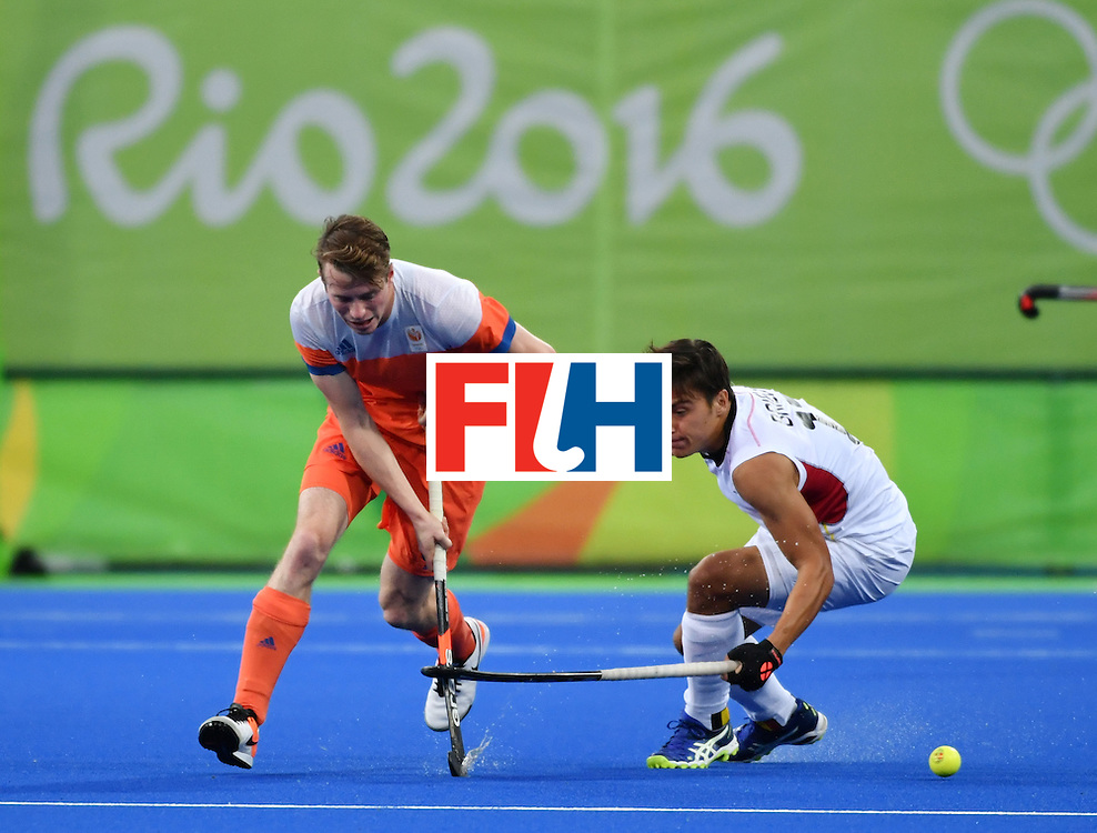 Netherland's Seve van Ass (L) vies with Belgium's Thomas Briels during the men's semifinal field hockey Belgium vs Netherlands match of the Rio 2016 Olympics Games at the Olympic Hockey Centre in Rio de Janeiro on August 16, 2016. / AFP / Pascal GUYOT        (Photo credit should read PASCAL GUYOT/AFP/Getty Images)