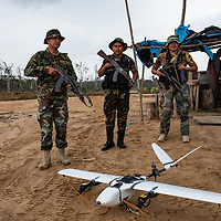 Peruvian National Police Special Forces members look on as CINCIA's fixed wing drone is prepared for its next mapping flight. Following Peru's February 2019 militarized crackdown on illegal and unofficial alluvial gold mining in the La Pampa region of Madre de Dios, Wake Forest University's Puerto Maldonado-based Centro de Innovación Científica Amazonia (CINCIA), a leading research institution for the development of technological innovation for biological conservation and environmental restoration in the Peruvian Amazon, is applying years of scientific research and technical experience related to understanding mercury contamination and managing Amazonian ecosystems. What they learn will help guide urgent remediation, restoration, and reforestation efforts that can also serve as models for how we address the tropic's most dramatically devastated landscapes around the world. La Pampa, Madre de Dios, Peru.