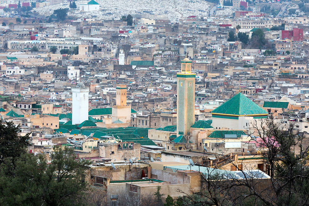 FEZ, MOROCCO - 1ST FEBRUARY 2018 -  View over the old Fez Medina, with the Al-Karaouine Mosque and University (building on the left with green tiled roof and white Minaret) and the Zawiya Moulay Idriss II (larger building on the right with pyramid roof).<br /> <br /> Established at the very beginnings of Morocco's oldest imperial city, the University of Al-Karaouine (also written as Al-Quaraouiyine and Al-Qarawiyyin) was founded in 859 and is considered by Unesco and the Guinness Book of World Records to be the oldest continually operating university in the world.