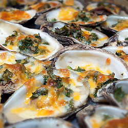 Cooked oysters with cheese and fresh herbs
